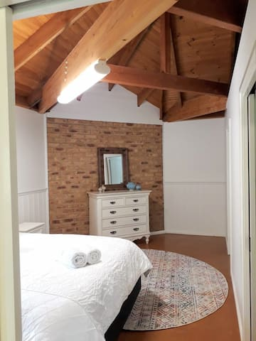Luxury bed with quality linens, gorgeous high wooden ceilings, walk in robe.