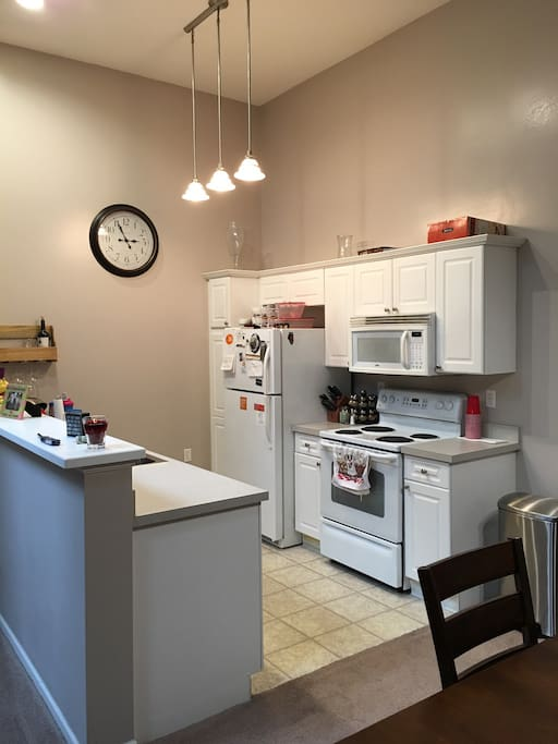 Kitchen with vaulted ceilings.  Electric stove and oven microwave fridge sink and dishwasher.