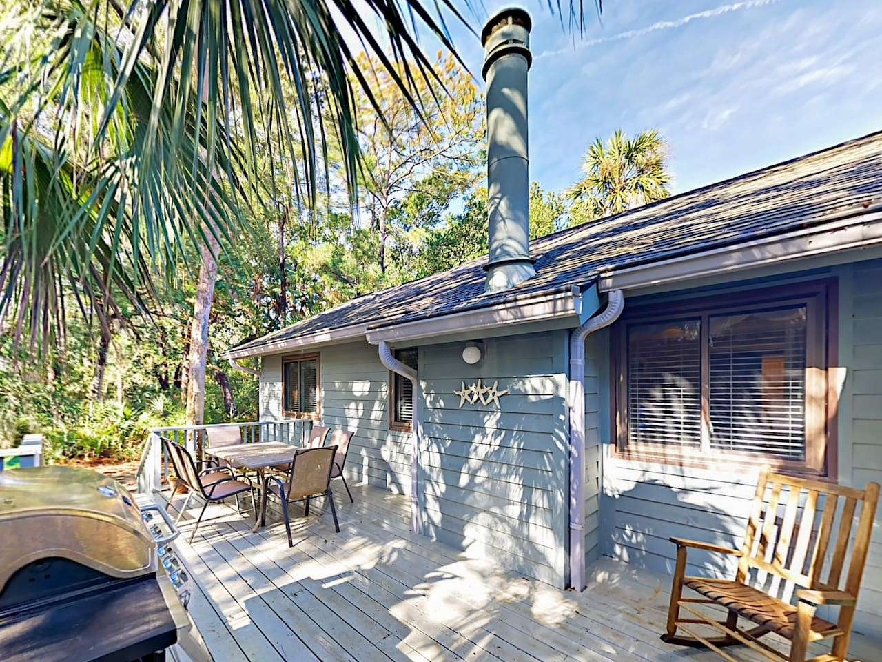 A private deck features a gas grill, and an outdoor dining table that seats 6.