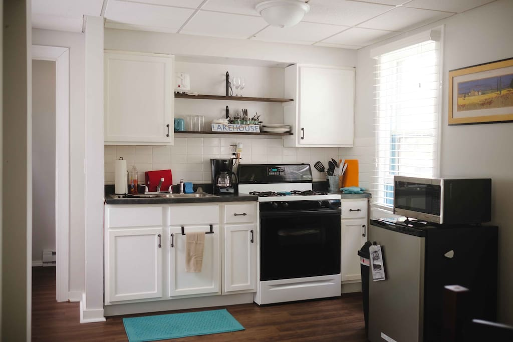 Full & furnished kitchen with gas stove, refrigerator, coffee maker.