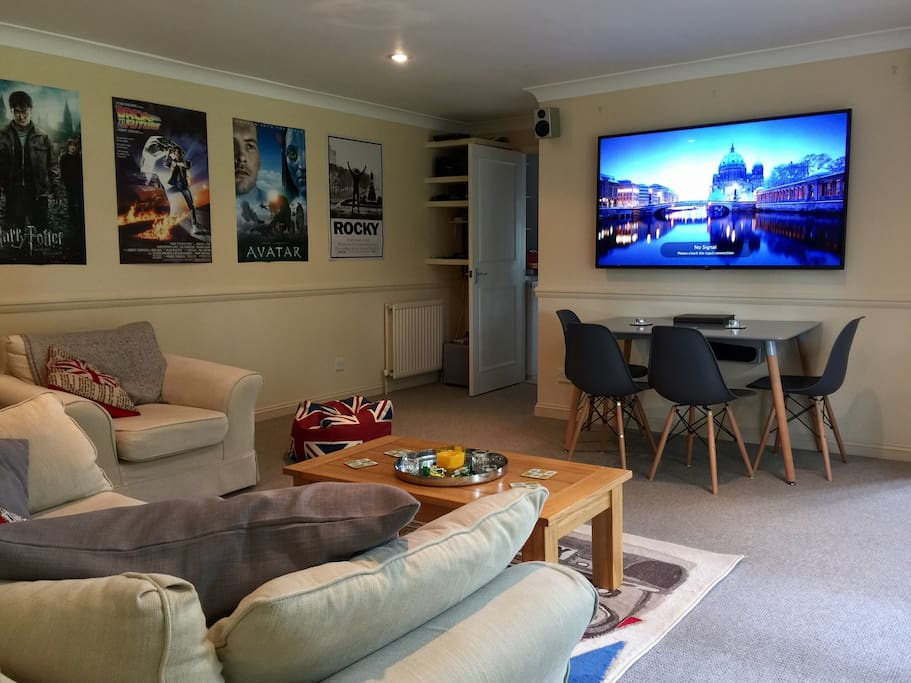 """The living room is a homely space including a dining table and chairs and comfy sofas to chill out in.  There is an entertainment system with a 66"""" ultra HD screen, DVD player, freesat TV, and Xbox."""