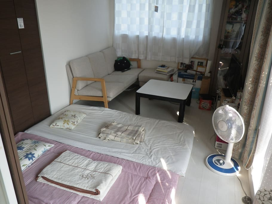 This is my living room, but there are privacy doors between it and the kitchen.  One or two people can be very comfortable here on Japanese style futons!  Sunny balcony on one side!