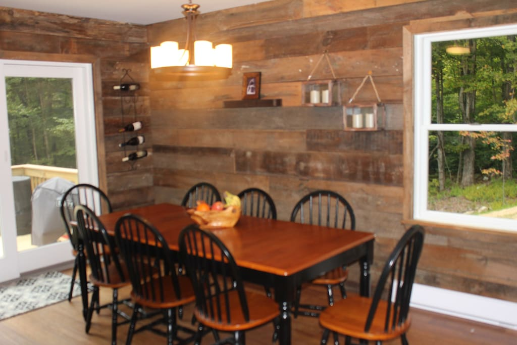 Reclaimed barnwood walls in dining area large table & sliders to outdoor deck