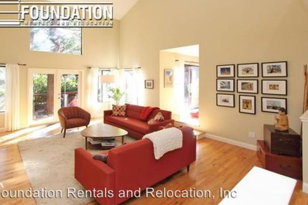 Spacious living room with working wood burning fireplace and cathedral ceilings - opens up to back yard