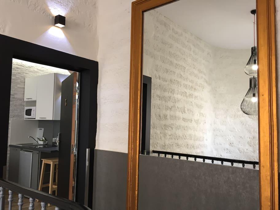 Palier / Entrée de la suite (appartement). Pierres de Castries apparentes murales et escaliers en pierres, dans maison de caractère au cœur de ville de Montpellier.