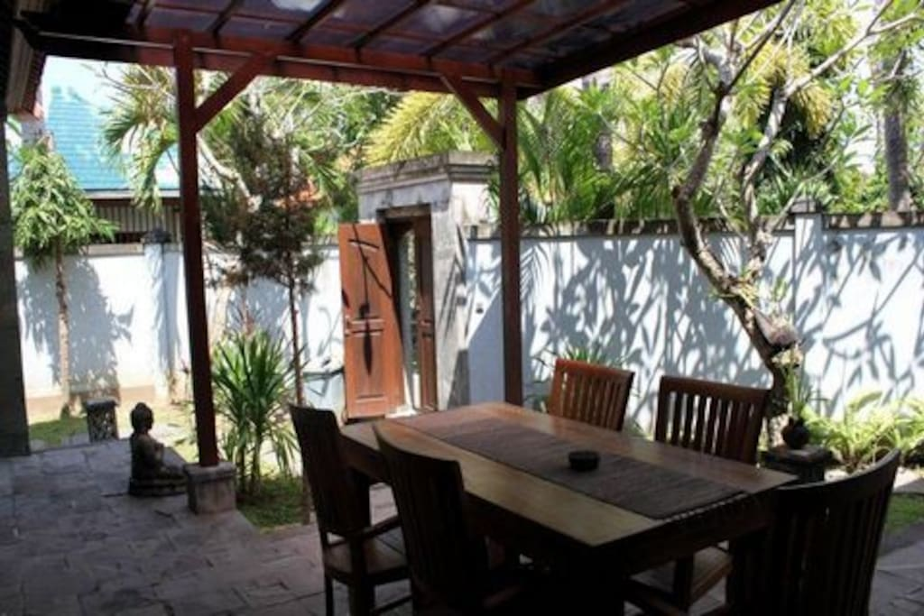 Covered terrace with dining table and private garden surrounded by a wall for safety and privacy