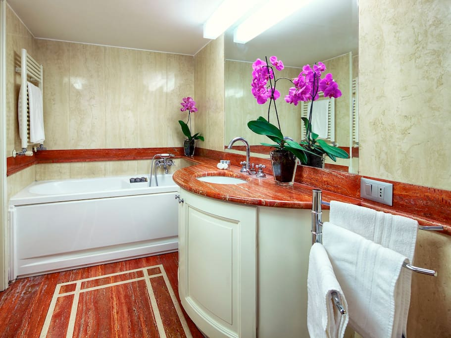 The private bathroom, with luxurious marble finishes and bath tub