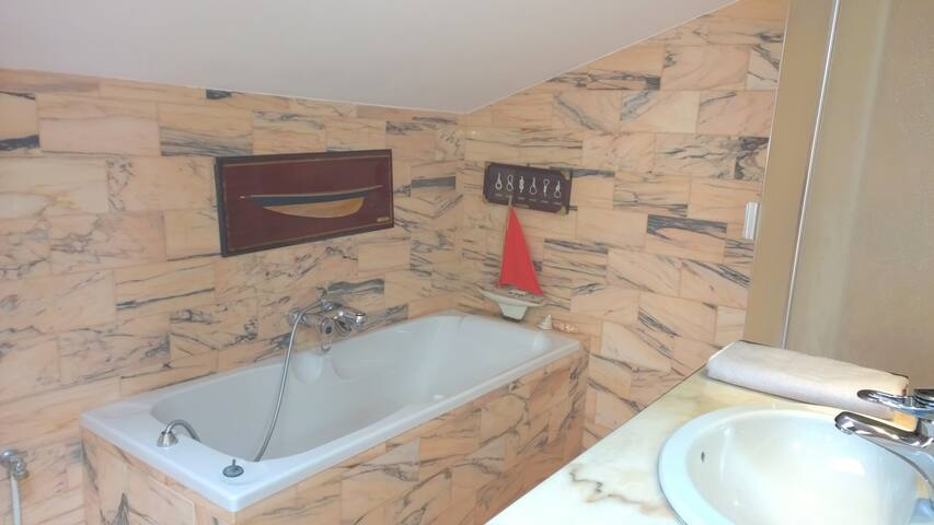 Grande salle de bain  en marbre rose.