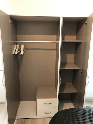Der Schrank mit vielen Bügeln bietet die Möglichkeit, Ihre Kleidung dort bequem aufzubewahren