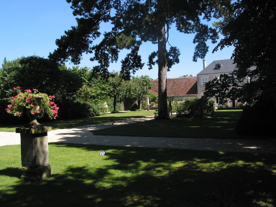 one view of the gardens, the cottage and the pool are on the left behind the trees .