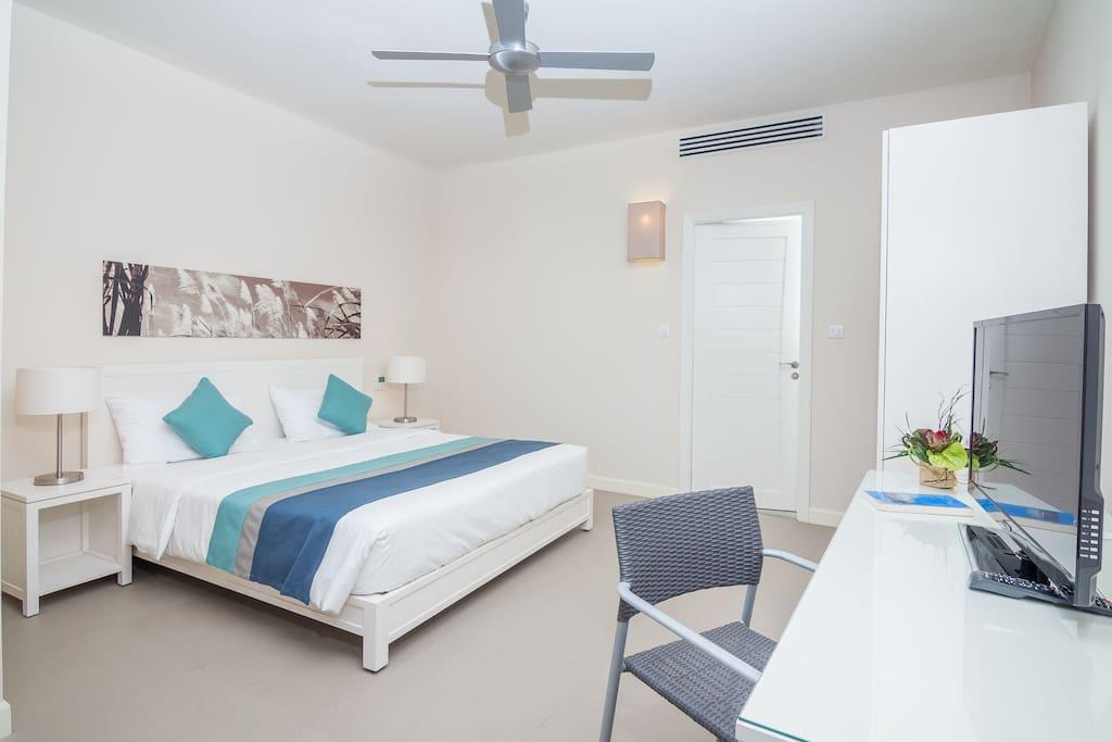 Coin couchage avec lit double, bureau, TV, clim et plafonnier