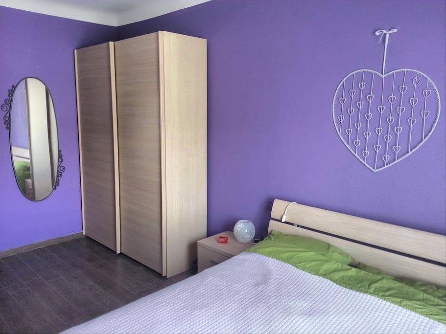 Camera da letto con ampio armadio e specchio a figura intera.