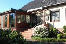 Hauseingang mit einem gemütlichen beheizbaren Wintergarten Kamin.