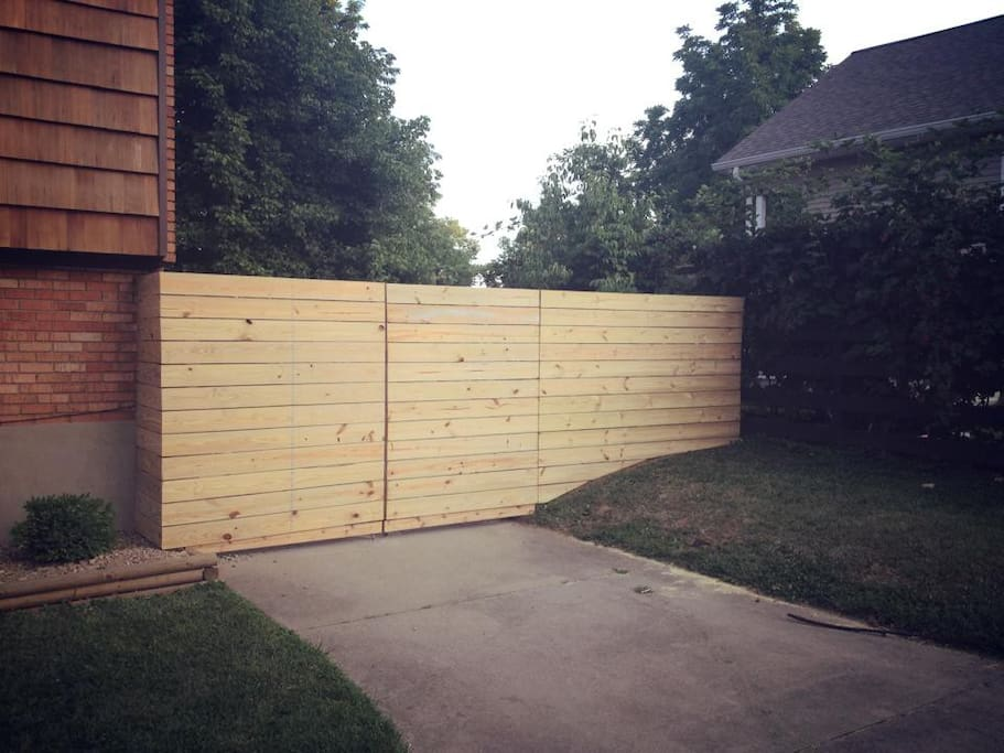 Privacy fence leading to large backyard w/ grill, fire pit, patio and outdoor dining furniture.