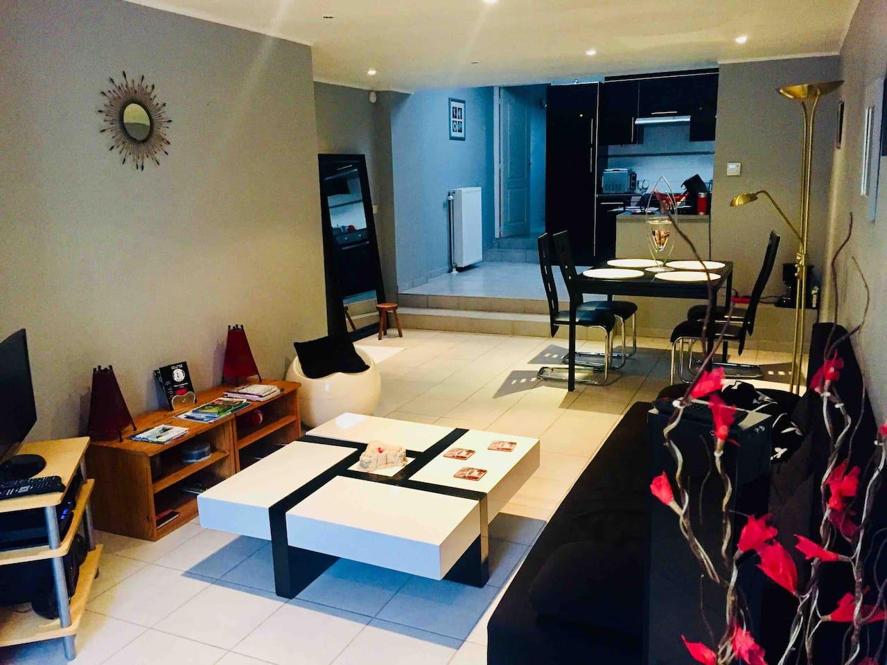 Vue d'ensemble salon, salle à manger, cuisine et porte du couloir donnant accès à la chambre, la sdb et le jardin.