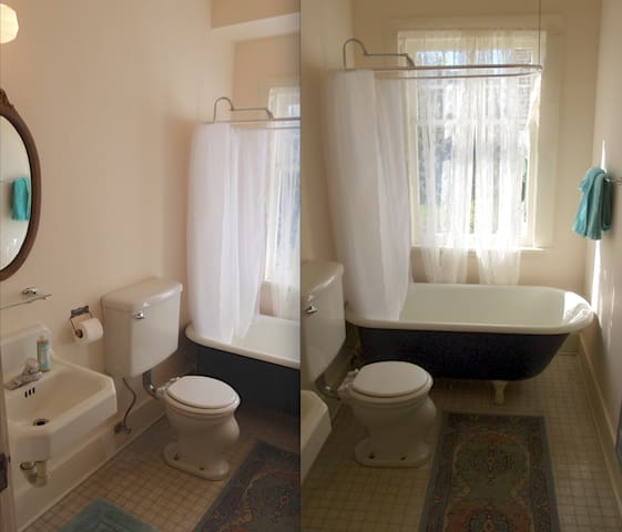 Bathroom with claw foot tub / shower adjacent the shared laundry room.