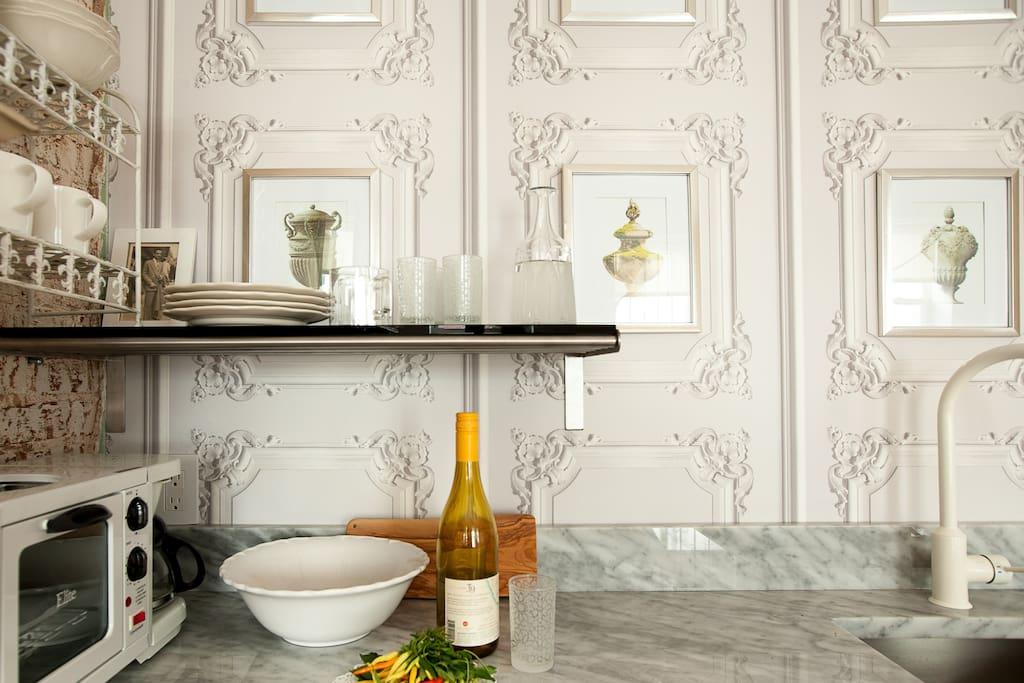 Trompe l'oeil wallpaper accents the convenient wet bar.