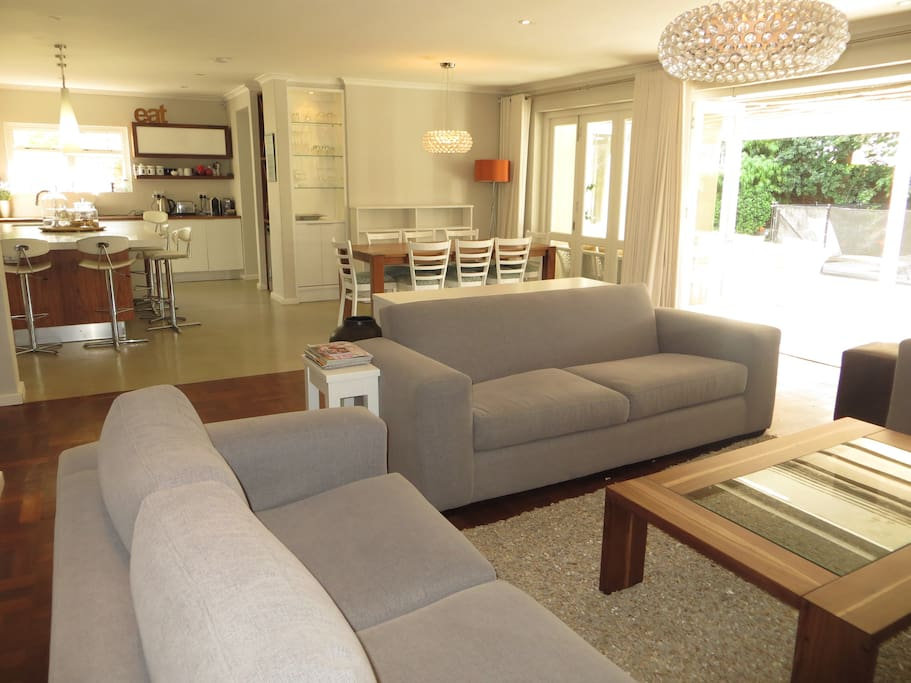 Open plan lounge, dining room and kitchen with folding doors to patio and pool area