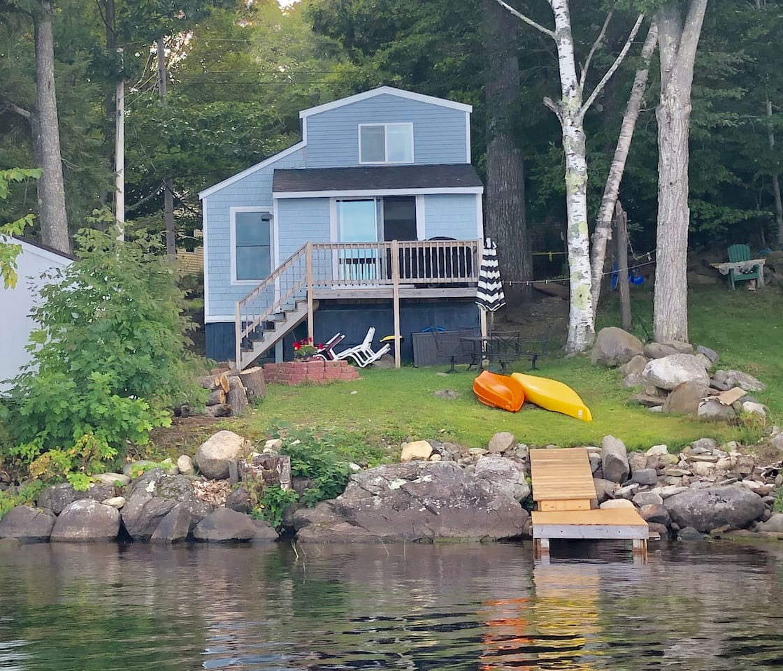 Lake side of cottage with outdoor seating and storage with cushions, kayaks, paddle board and grill available