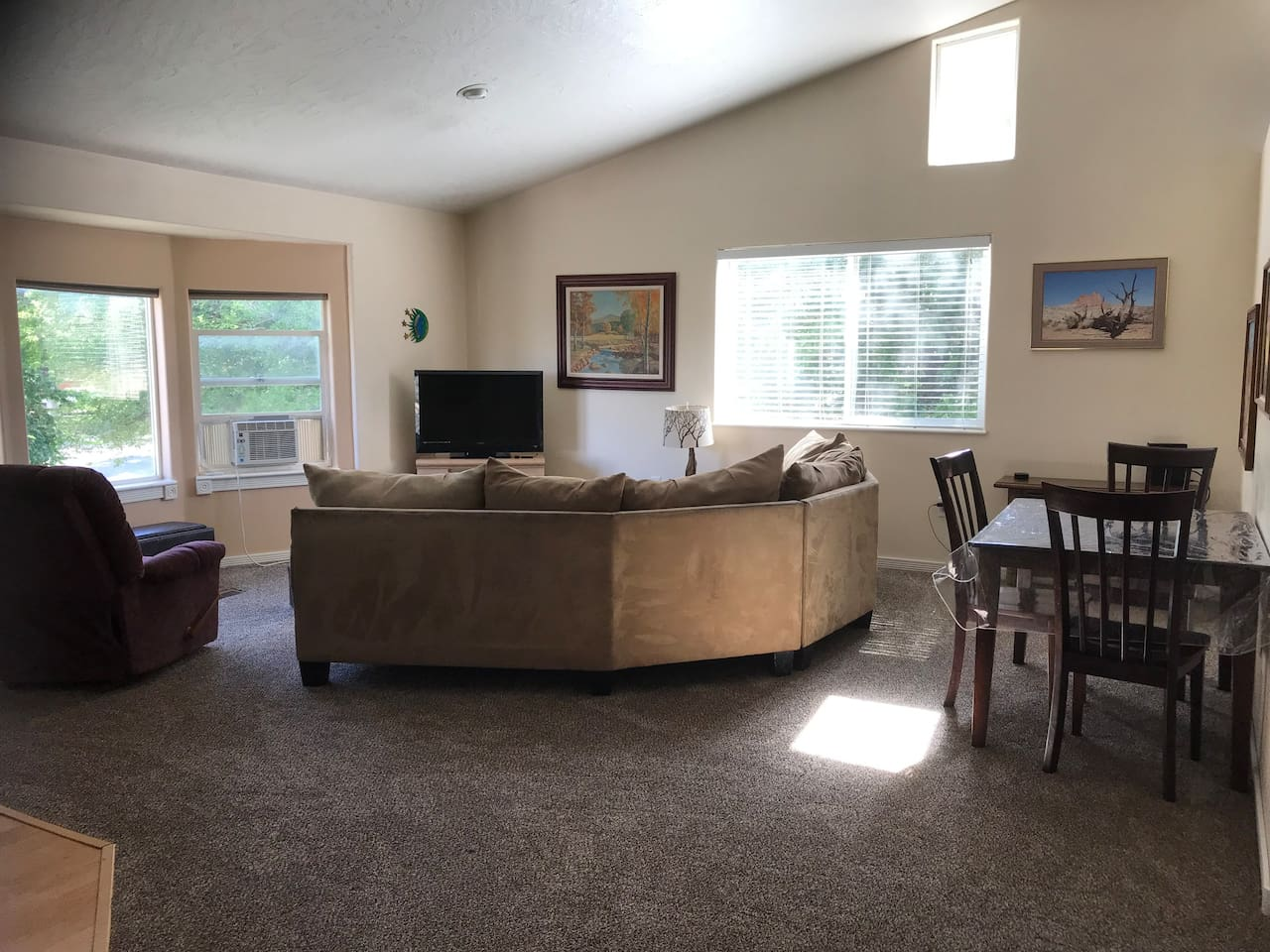 Large spacious living room with games in cabinet by wrap around bar and TV and lots of windows.