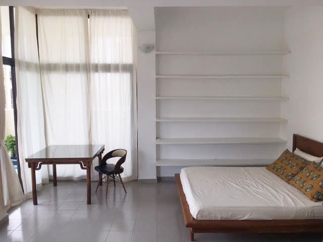 Table, chair, queen sized bed and wall of shelving