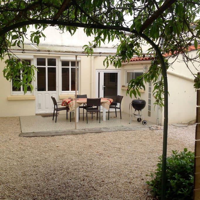 La maison et sa terrasse couverte vue du jardin