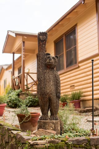 """The carved bear welcomes you to his """"Hilltop Hideaway""""."""
