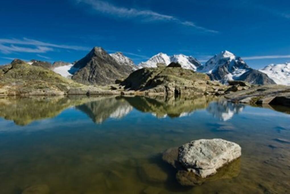 Il cielo azzurro sovrasta le catene montuose, creando un'atmosfera piacevole e rilassante.