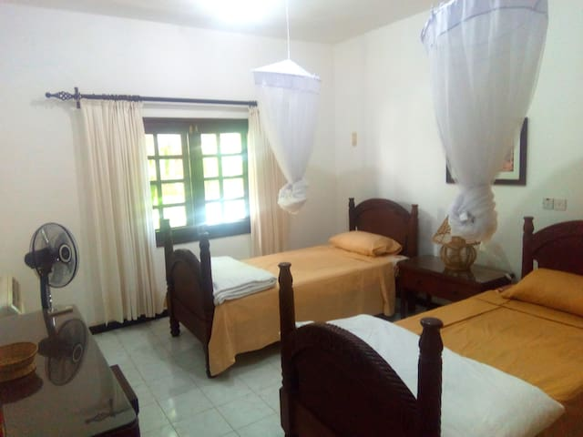 Air-conditioned Bedroom 2 with 2 Single Beds,a fan,mosquito nets installed.