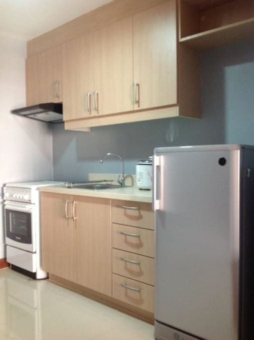 Kitchen with appliances (Refrigerator, rice cooker, gas range, range hood, microwave).