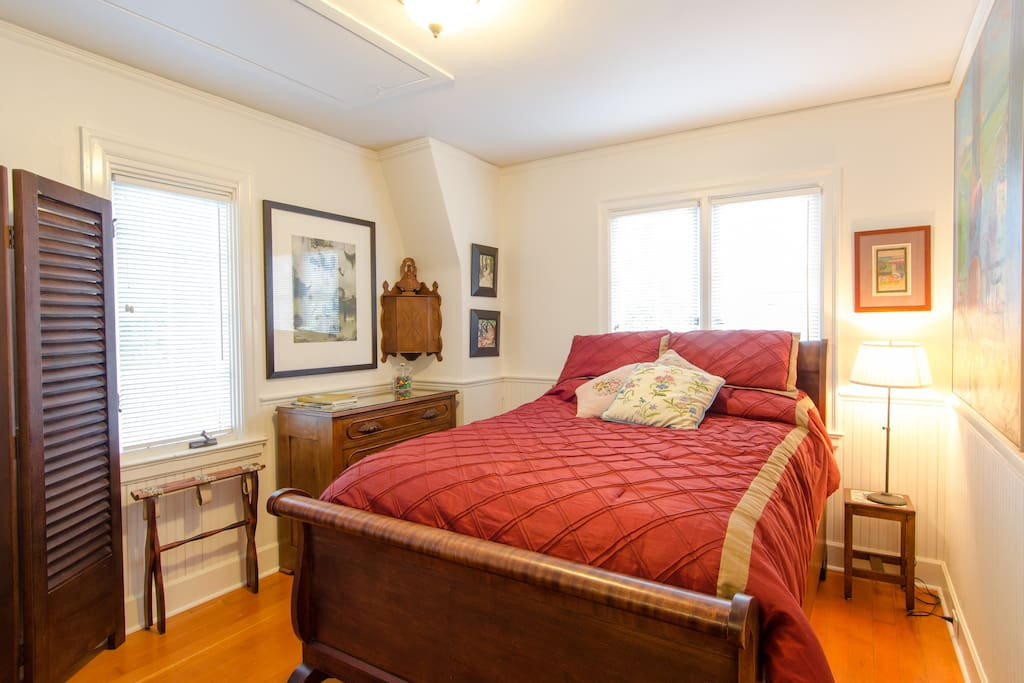 The bedroom is filled with beautiful antiques and original artwork.