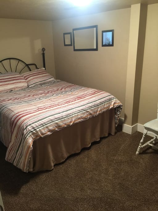BEDROOM 2 with another comfy queen bed. This is a larger room with closet, iron and ironing board, and a pack-n-play.
