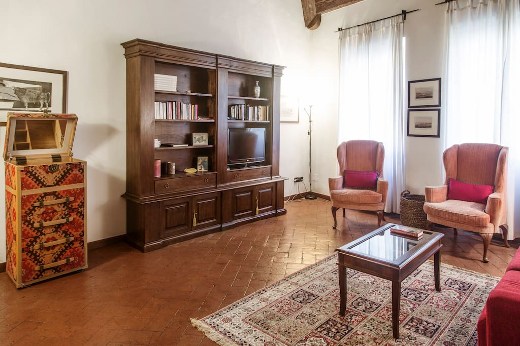 "Spacious high ceiling living room, furnished with a mix of classical and modern furnitures. The floor is traditional ""cotto fiorentino"" (Florentine fired brick). Plenty of light comes from two large windows facing the main road"