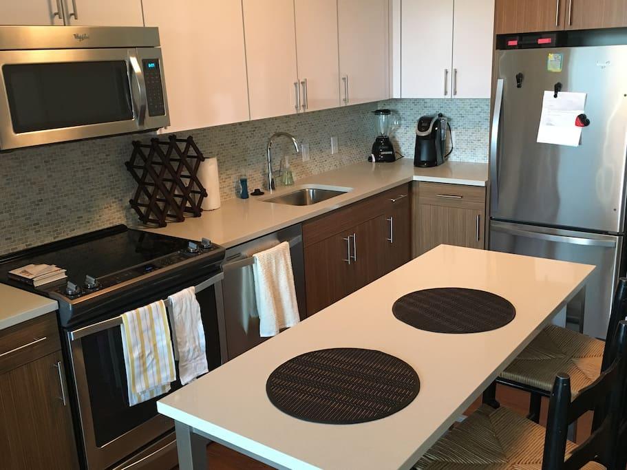 Modern, clean kitchen with brand new appliances.