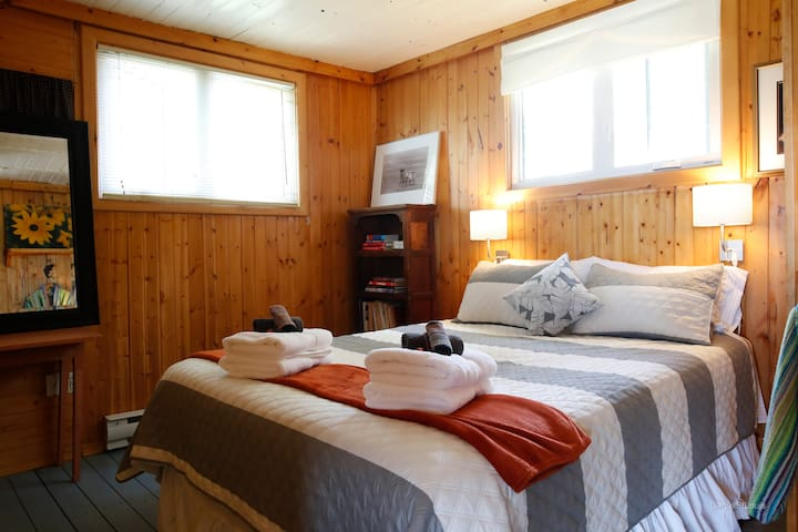 The master bedroom has two windows , a comfy clean bed and a mid size closet