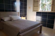 Quarto com cama de casal, TV, ar-condicionado e guarda-roupas