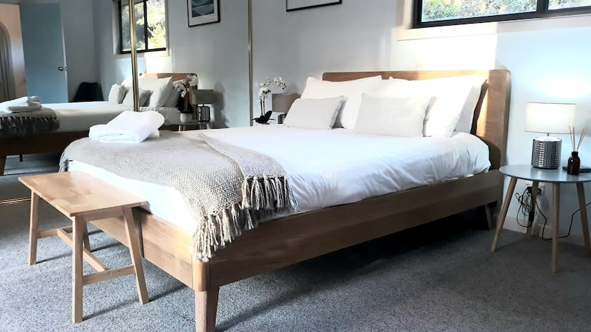 """""""Wayilahr Room"""" is our master queen room, watch the black cockatoos feeding on nearby banksia from the upper deck. A genourously sized room furnished with a queen bed, bedside tables and lamps and a large robe."""