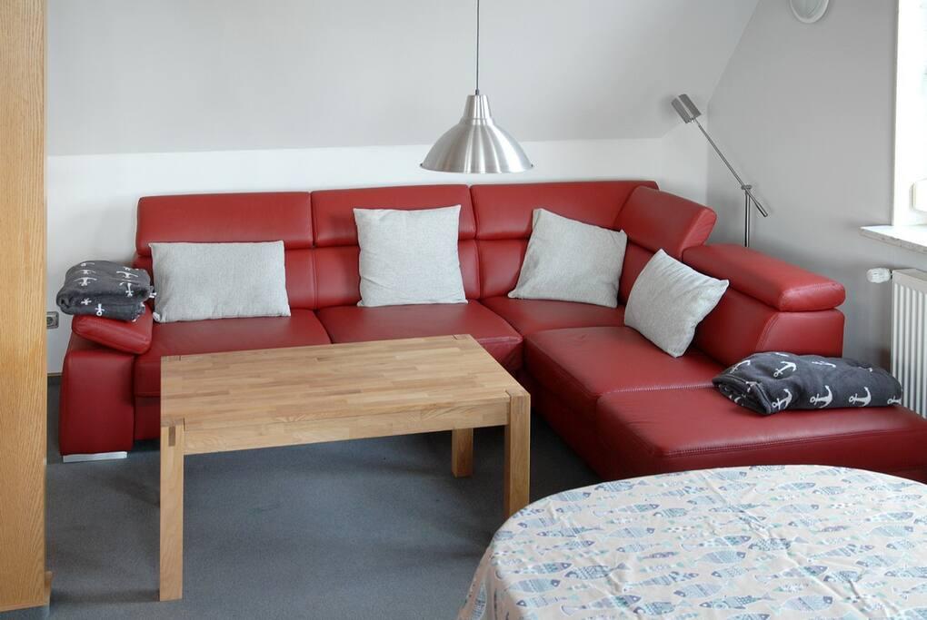 Im großzügigen Wohnraum lädt ein Lederecksofa zum Entspannen ein.