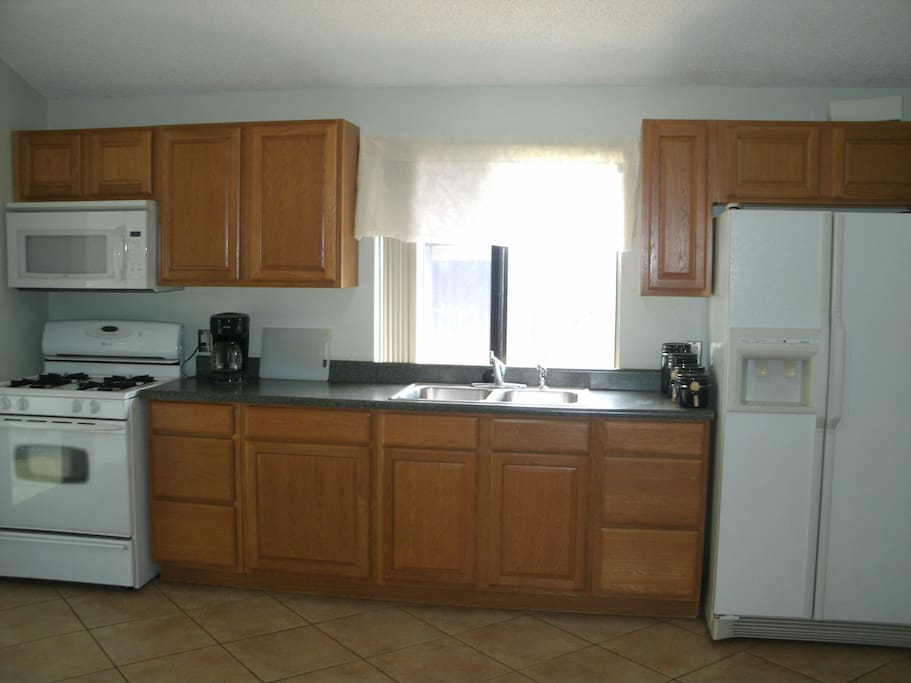 Kitchen with full size refrigerator and range and microwave.  Coffee maker, toaster, pots and pans. Dishes and glasses too.