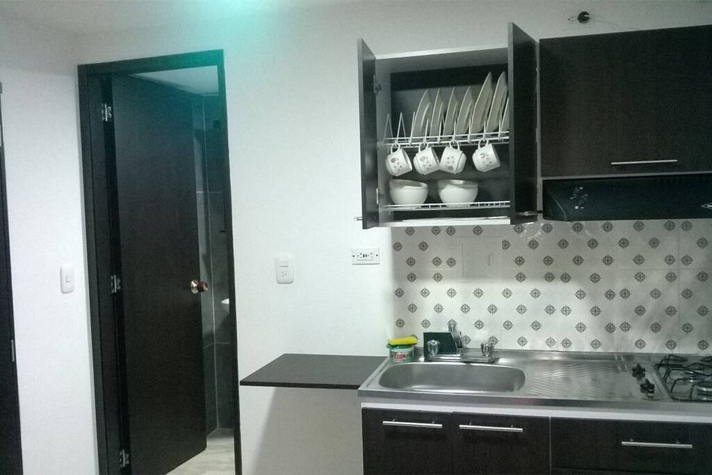 Cocina con juego completo de platos, ollas, cubiertos y nevera. La puerta es la entrada del baño