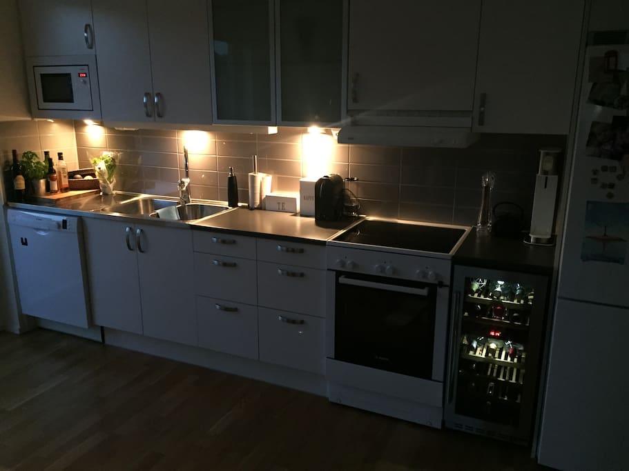 Fullt utrustat kök, öppet mot vardagsrum.