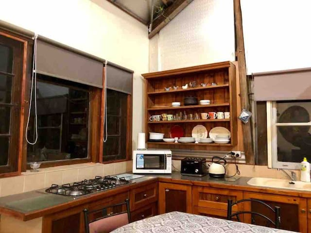 large gas stove top in the kitchen. microwave, toaster, kettle and double sink also seen here