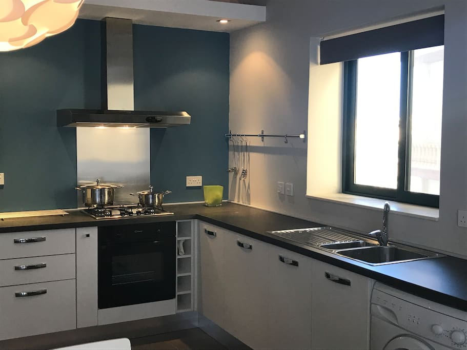 Kitchen with fridge/freezer, electric oven, gas cooktop dishwasher and washing machine.