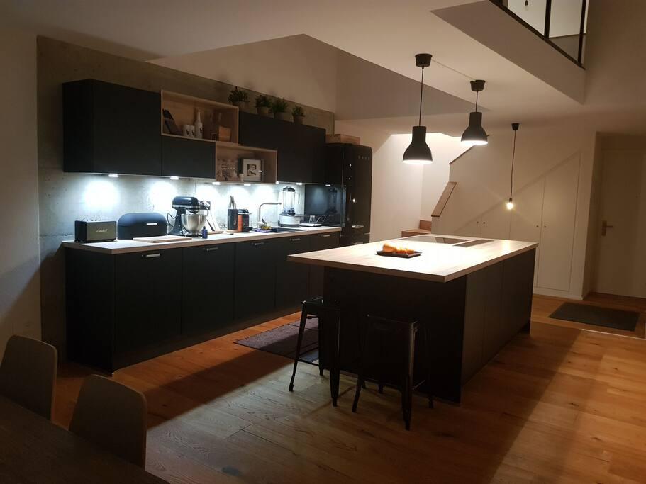cuisine avec ilôt central, bar et salle à manger lumineuse
