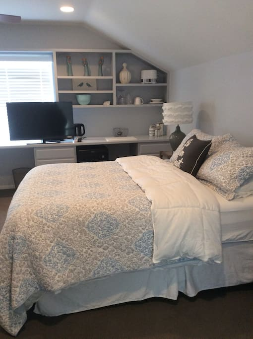 Plush queen bed, TV, desk and kitchenette area