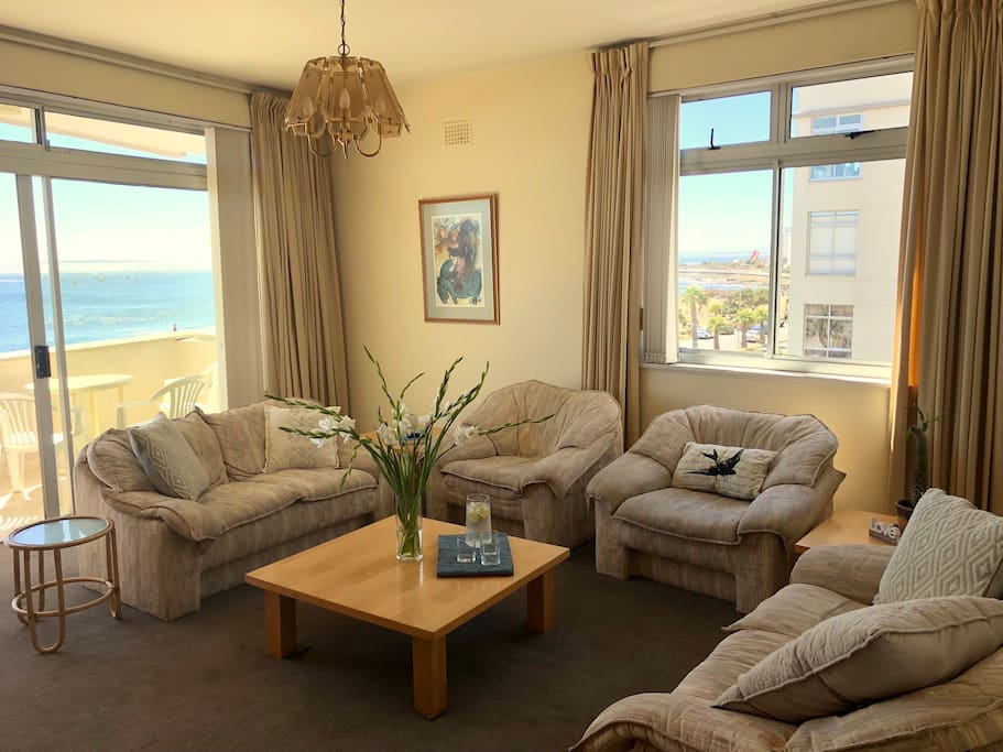 Comfortable, spacious living room with ample seating and view of waterfront