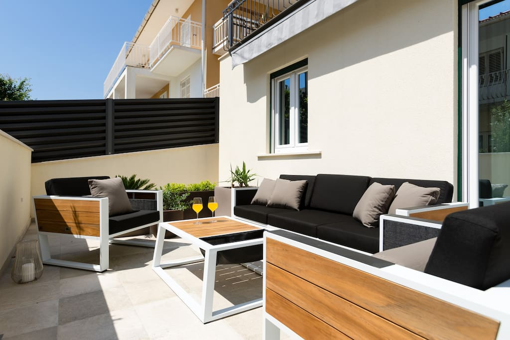 Private 46 m² terrace in front of the apartment with 2 sunbeds, three-seater, 2 armchairs and a table