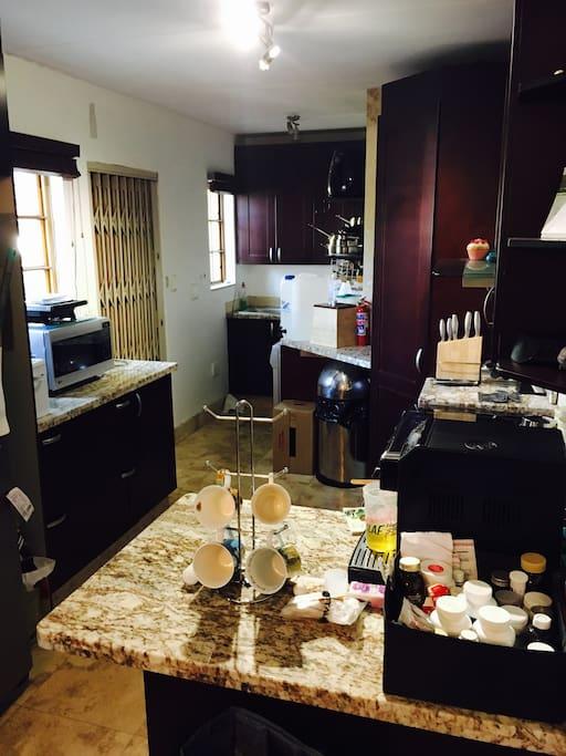 Kitchen, dishwasher , washing machine, double door fridge opening up outside to washing line