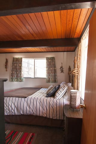 Bedroom 2 downstairs is decorated in woodsy vibes with a handmade log bedframe and other rustic accents.  100% cotton bedding feels just right.