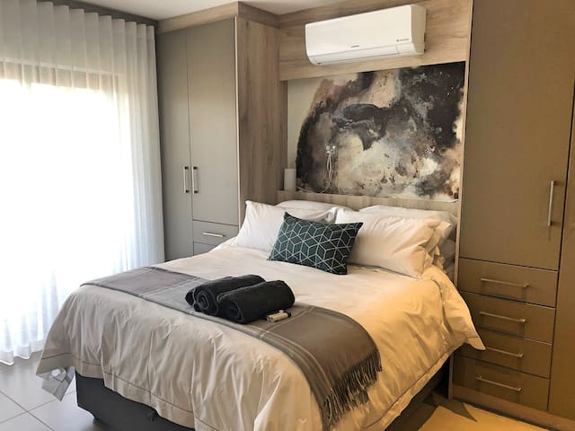 Queen-sized bed with fresh crisp linen and towels, and air conditioning